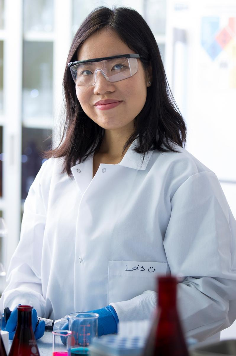 Girl in lab smiling wearing safety glasses
